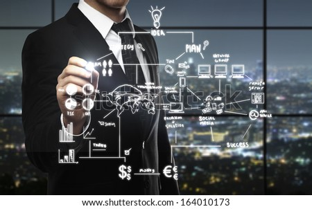businessman drawing business strategy in night office