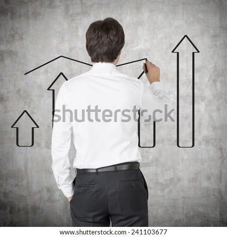 businessman drawing chart and arrows on wall