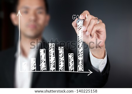 Businessman drawing chart on whiteboard - stock photo