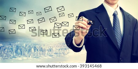 Businessman drawing E-mail concept on blurred abstract background  - stock photo