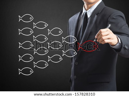 Businessman drawing fishes in group leadership concept - stock photo