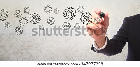Businessman drawing gear sketch with a marker - stock photo