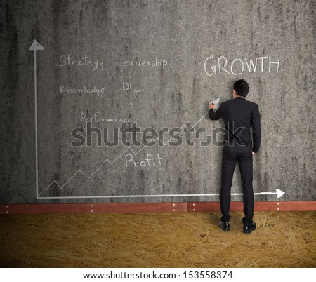 businessman drawing graph and  concept  on old wall - stock photo