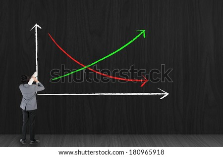 Businessman drawing growing green graph - stock photo