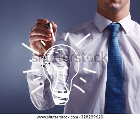 Businessman drawing idea light bulb, close up - stock photo