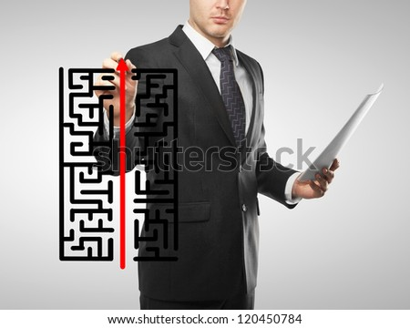 businessman drawing labyrinth and red arrow - stock photo
