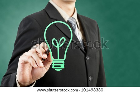 Businessman drawing light bulb green concept - stock photo