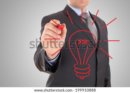 Businessman drawing lightbulb - stock photo