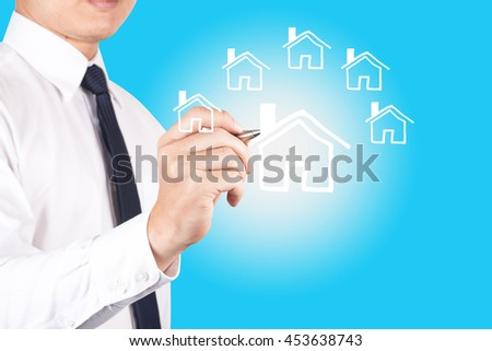 businessman drawing model house with pen.