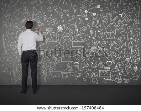 businessman drawing on the wall by chalk