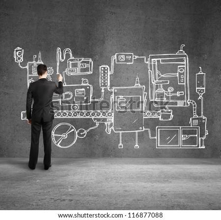 businessman drawing plan mechanism on wall - stock photo
