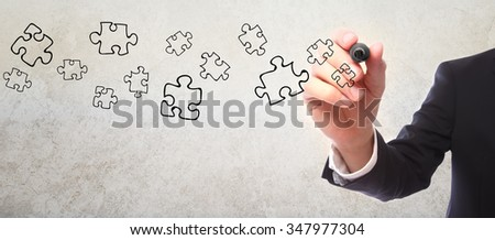 Businessman drawing puzzle piece sketch with a marker - stock photo