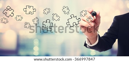 Businessman drawing Puzzles concept on blurred abstract background