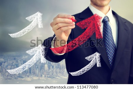 Businessman drawing rising arrows in the city - stock photo