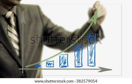 Businessman drawing rising graph, development and growth concept, increase of positive indicators in entrepreneurship. - stock photo