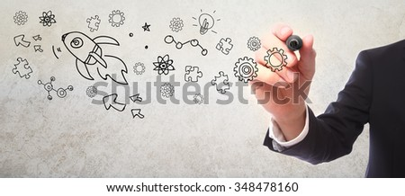 Businessman drawing rocket sketch with a marker - stock photo