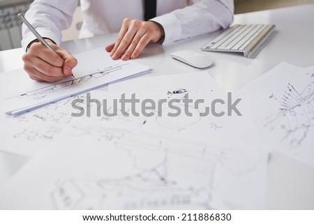 Businessman drawing sketches at workplace - stock photo
