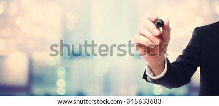 Businessman drawing something with a black maker on blurred abstract background