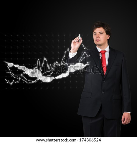 Businessman drawing stock fluctuations in a glass screen - stock photo