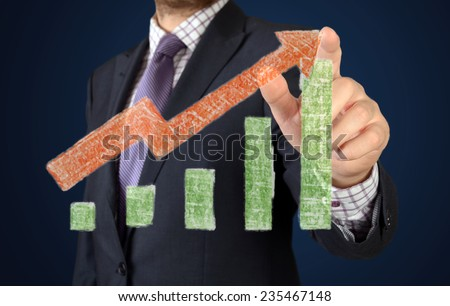 Businessman drawing success graph on virtual futuristic computer display  - stock photo