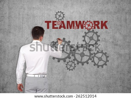 businessman drawing teamwork concept on concrete wall - stock photo