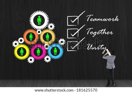 Businessman drawing teamwork with gear and employee symbol on black wall