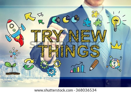 Businessman drawing Try New Things concept on a light blue colored screen - stock photo