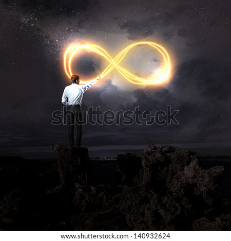 Businessman draws a glowing signs in the dark sky - stock photo