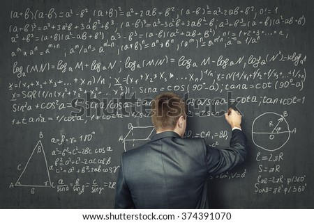 Businessman draws on concrete wall of the mathematical formulas. Business and education concept