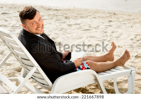 Businessman dressed in suit and shorts working with laptop on the sunbed at the beach - stock photo
