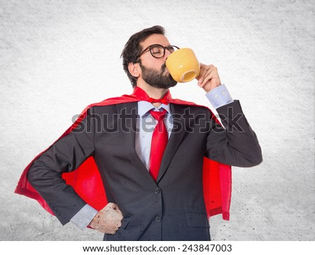 Businessman dressed like superhero drinking coffee
