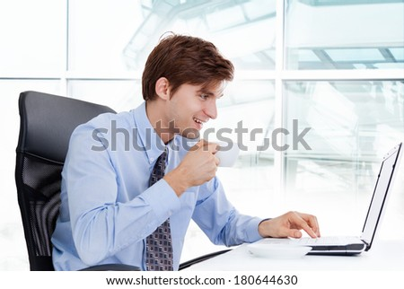 businessman drink coffee or tea hold cup sitting at desk in office using laptop computer, handsome young business man happy smile - stock photo