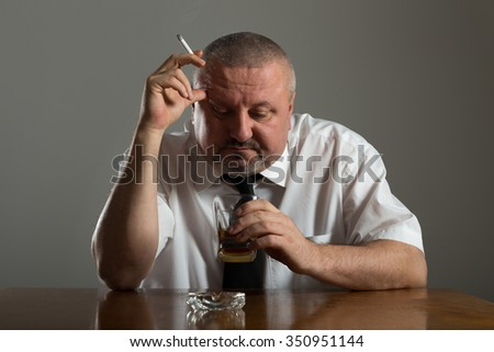 Businessman drinking alcohol and smoking cigarette - stock photo