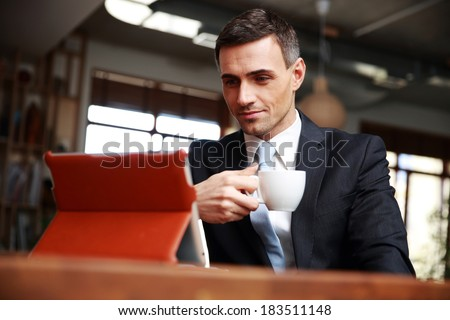 Businessman drinking coffee and reading news in cafe - stock photo