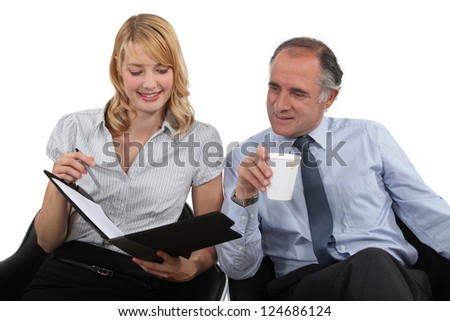 businessman drinking coffee and talking to his assistant - stock photo
