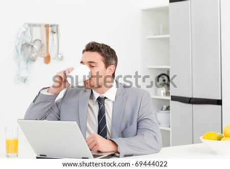 Businessman drinking while he is looking at his laptop at home