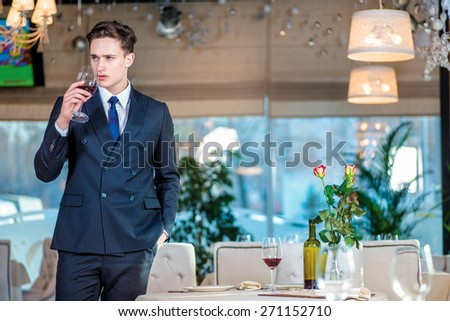 Businessman drinking wine. Young man businessman in formal wear standing in a restaurant while holding a glass of wine and looking at the camera - stock photo