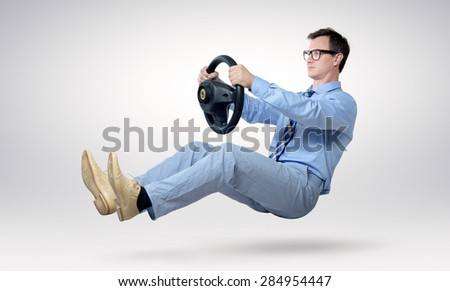 Businessman driver in glasses and tie with a wheel