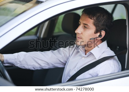 Businessman driving a car with blue-tooth hands-free