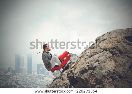 Businessman driving a fast car in a mountain - stock photo