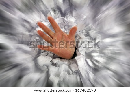 Businessman drowning in paperwork reaching for assistance and support - stock photo