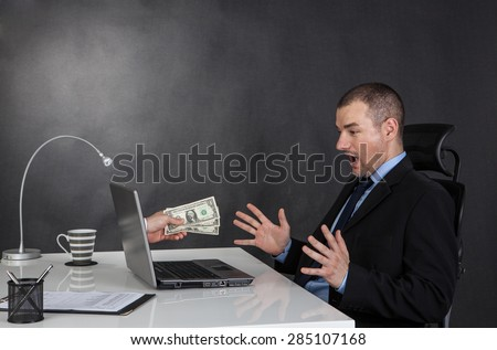 Businessman earning money on network.  He is receiving dolar cash over internet. - stock photo