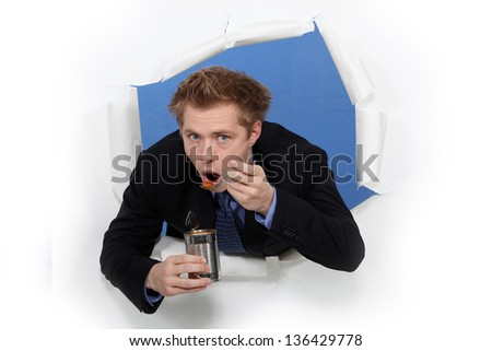 Businessman eating beans from a tin - stock photo