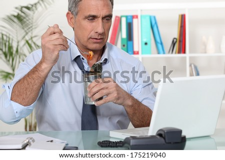Businessman eating food - stock photo