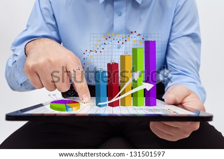 Businessman editing the annual report charts - working on a tablet computer