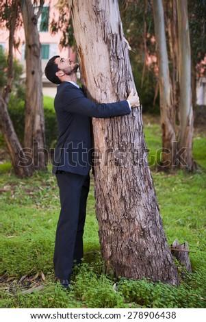 Businessman embrace a tree trunk - stock photo