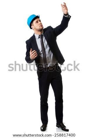 Businessman engineer in hard hat showing copyspace. - stock photo