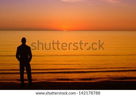 Businessman enjoying the sunrise before going to work - stock photo