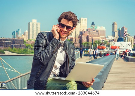 Businessman enjoying working outside. Wearing leather jacket, sunglasses, a guy with beard, sitting on bench at harbor, working on laptop computer, talking on phone in the same time. Instagram effect. - stock photo