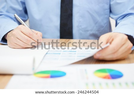 Businessman examines data and numbers and finalizing report - stock photo